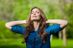 Beautiful woman facing the sun with hands clasped behind her head on a forest background
